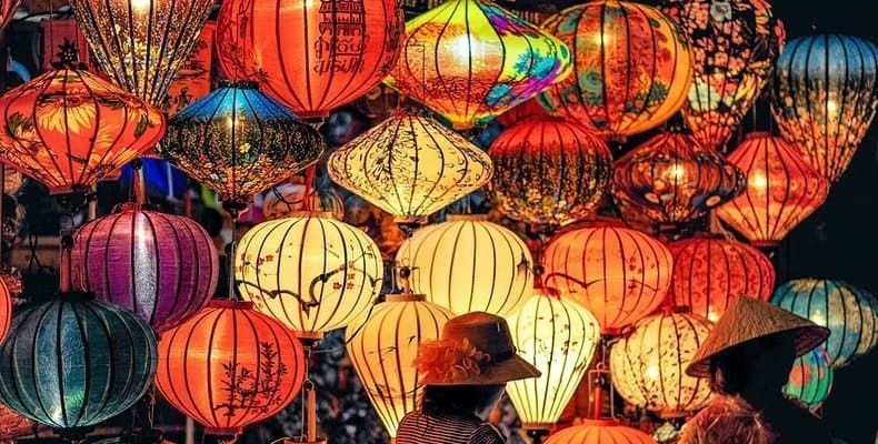Two people standing in front of multi colored lanterns showing the teaching of different cultures.