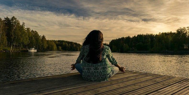 Woman doing yoga on a lake dock pondering work life balance tips.